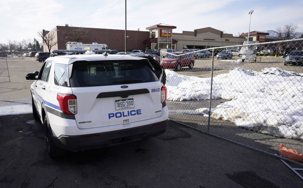 Police drive past a makeshift fence put up around the parking lot outside a King Soopers grocery store where a mass shooting took place Tuesday, March...