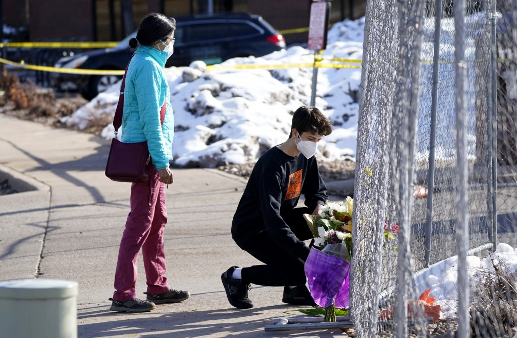 Caron Trout, left, of Boulder, Colo., looks on as her son, Beck, places a bouquet at a small memorial along a makeshift fence put up around the parkin...