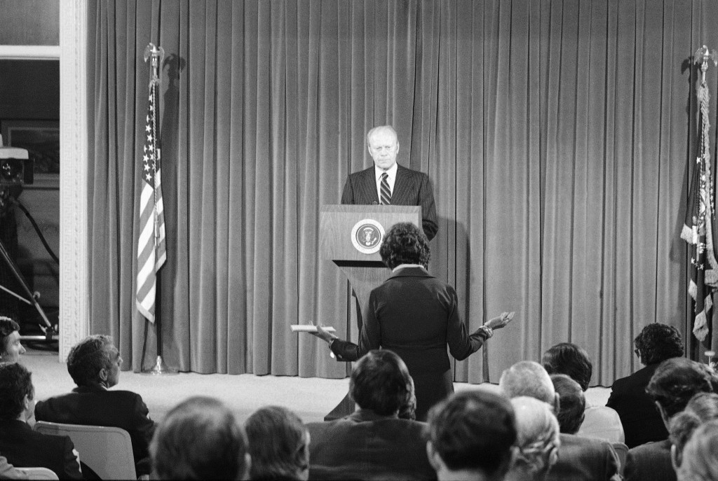 FILE - In this Oct. 9, 1975, file photo President Gerald Ford listens to a news reporter's question during a news conference at the Executive Office b...