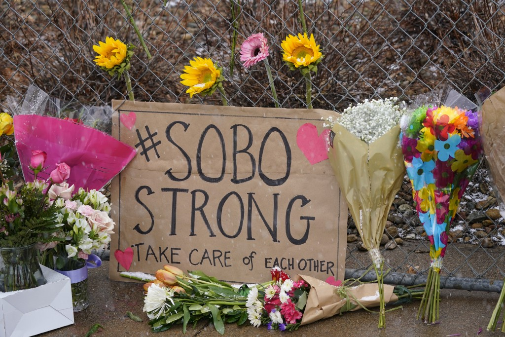 A sign from residents of south Boulder stands amid bouquets left along a fence put up around the parking lot where a mass shooting took place in a Kin...
