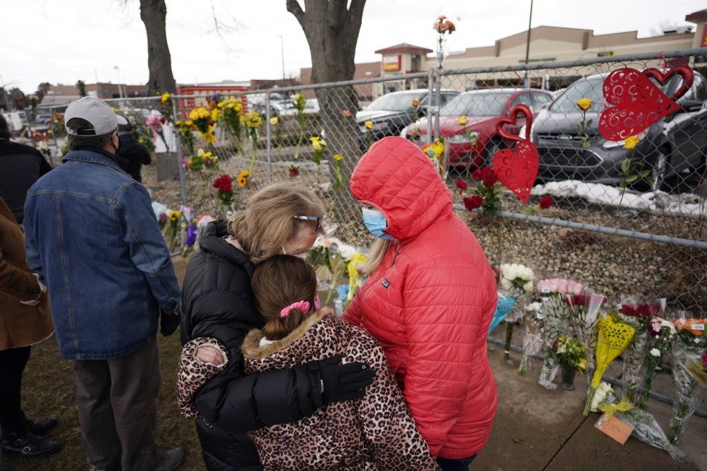 Mourners embrace after leaving bouquets on a fence put up around the parking lot where a mass shooting took place in a King Soopers grocery store Tues...