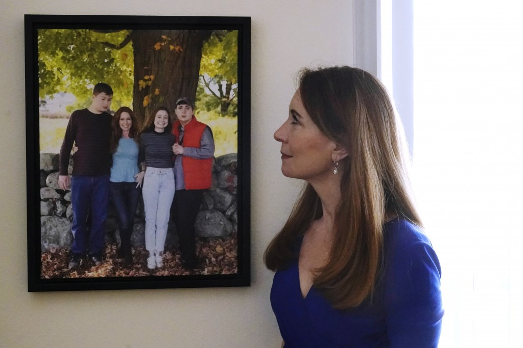 Maura Sullivan looks at a photograph of her children, Tyler, Gillian and Neil, at her home, Friday, March 19, 2021, in Lexington, Mass. The memory of ...