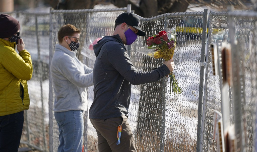 Kiefer Johnson places a bouquet of flowers into a makeshift fence put up around the parking lot outside a King Soopers grocery store where a mass shoo...