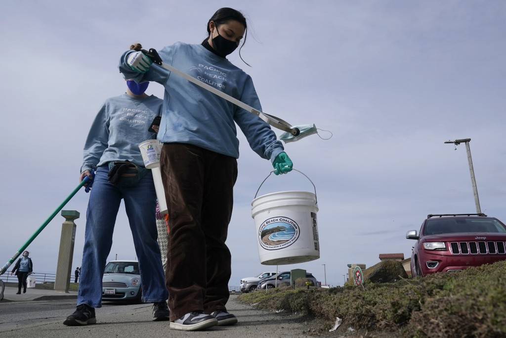 Pacifica Beach Coalition volunteer Amaelia Bringas, 16, picks up a face mask while picking up trash near Sharp Park Beach in Pacifica, Calif., Wednesd...