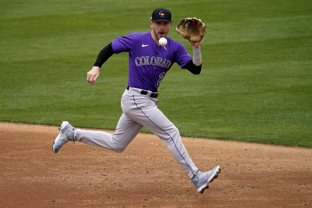 Colorado Rockies' Trevor Story fields a ground out hit by Oakland Athletics' Jed Lowrie during the second inning of a spring training baseball game, T...