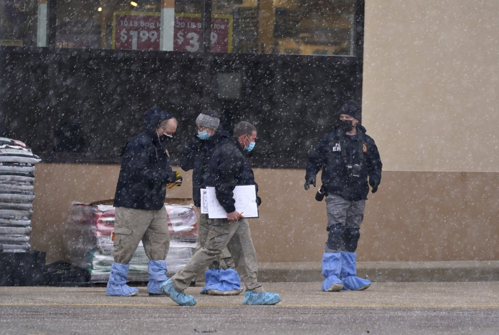 Investigators deal with light snow as they collect evidence in the parking lot where a mass shooting took place in a King Soopers grocery store Tuesda...