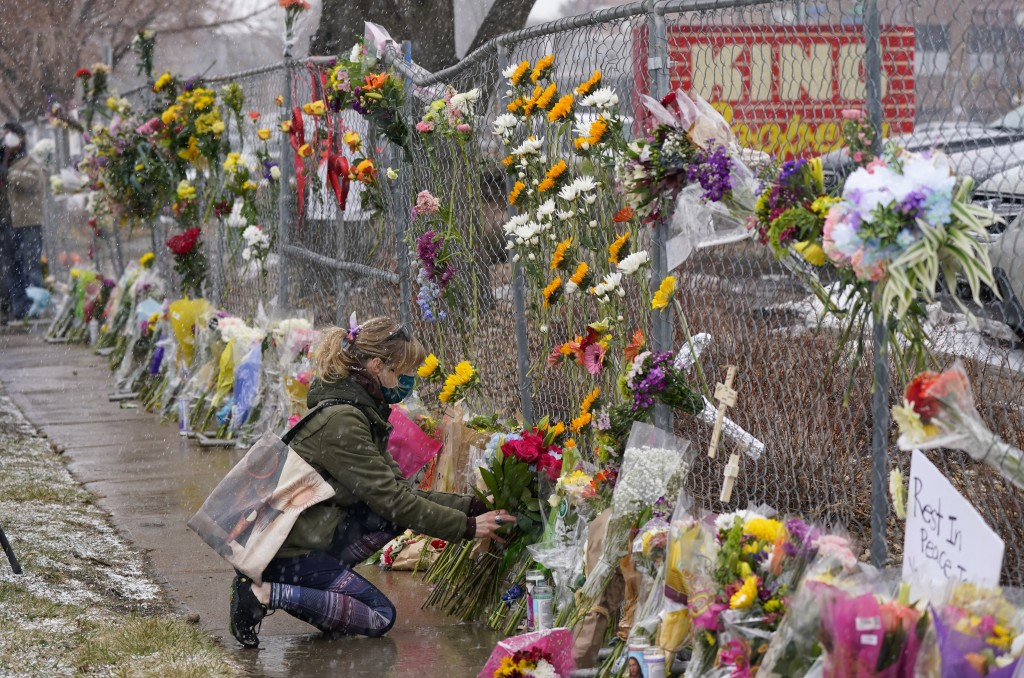 A mourner leaves a bouquet of flowers along a fence put up around the parking lot where a mass shooting took place in a King Soopers grocery store Tue...