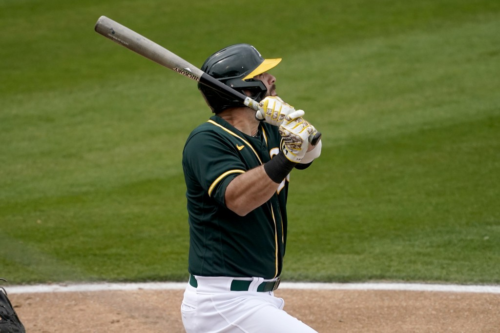 Oakland Athletics' Mitch Moreland follows through on a double against the Colorado Rockies during the second inning of a spring training baseball game...
