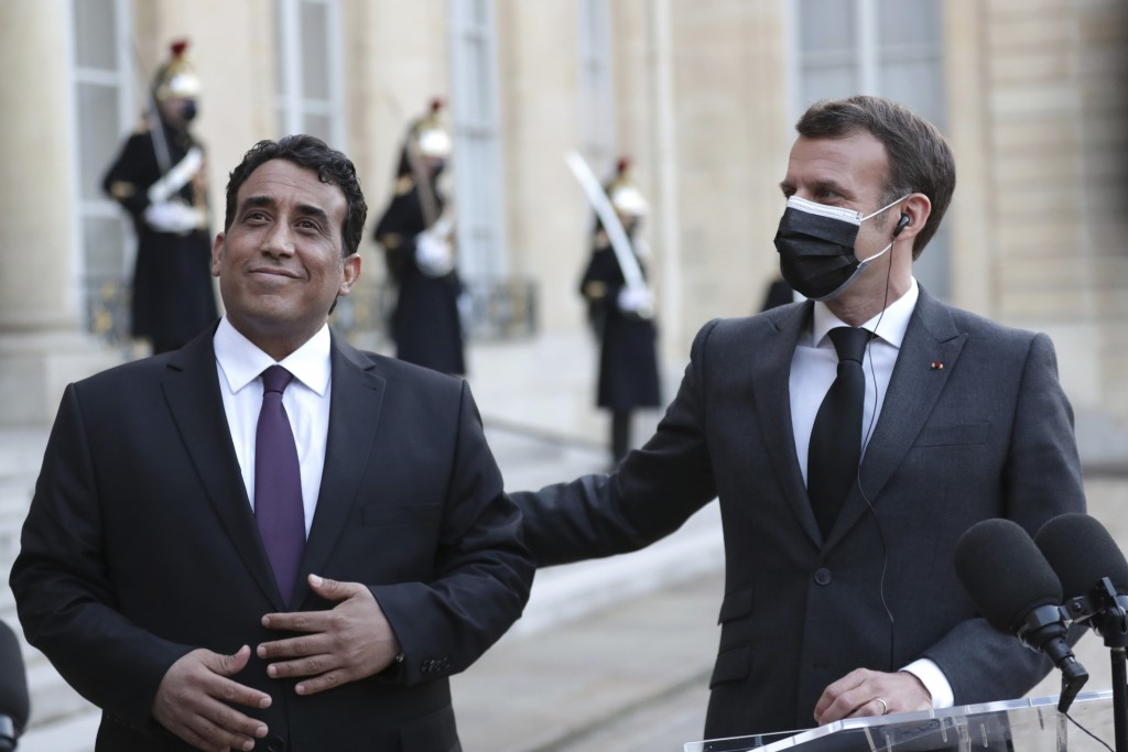 French President Emmanuel Macron, right, and Mohammad Younes Menfi, president of Libya's Presidential Council, left, after a meeting, at the Elysee Pa...