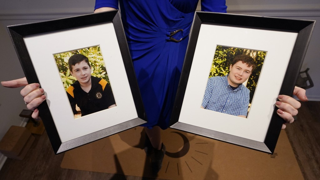 Maura Sullivan holds up photographs of her sons Neil, 19, left, and Tyler, 17, at her home, Friday, March 19, 2021, in Lexington, Mass. The memory of ...
