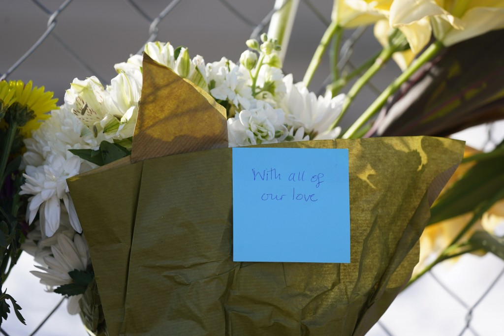 A message is taped to a bouquet left by aron and Beck Trout at a small memorial along a makeshift fence put up around the parking lot outside a King S...
