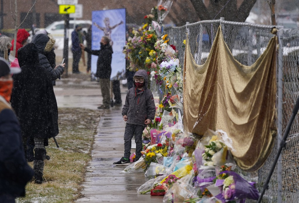 Mourners leave bouquets on a fence put up around the parking lot where a mass shooting took place the day before in a King Soopers grocery store Tuesd...