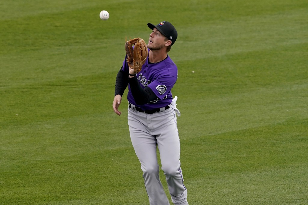 Colorado Rockies second baseman Ryan McMahon fields a fly-out hit by Oakland Athletics' Ramon Laureano during the first inning of a spring training ba...