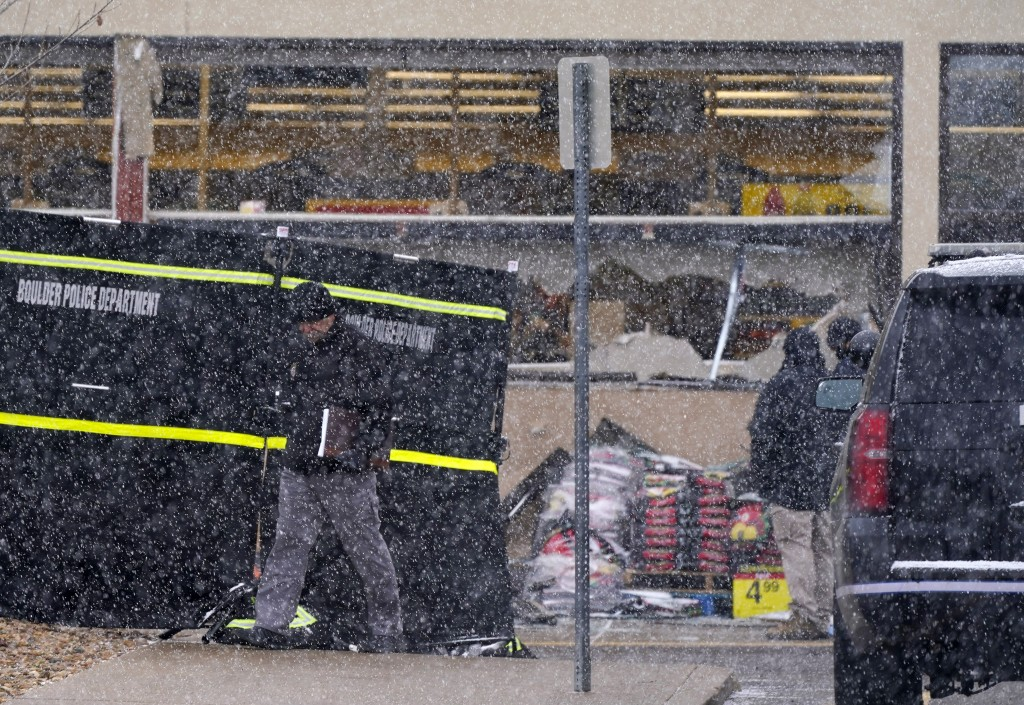 A snow squall envelops investigators as they collect evidence around the parking lot where a mass shooting took place in a King Soopers grocery store ...