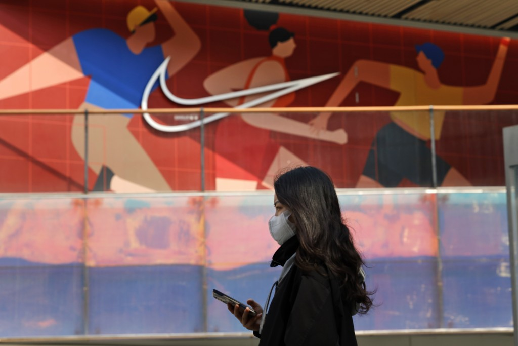A woman wearing a mask passes by a Nike store in Beijing on Thursday, March 25, 2021. China's ruling Communist Party is lashing out at H&M and...