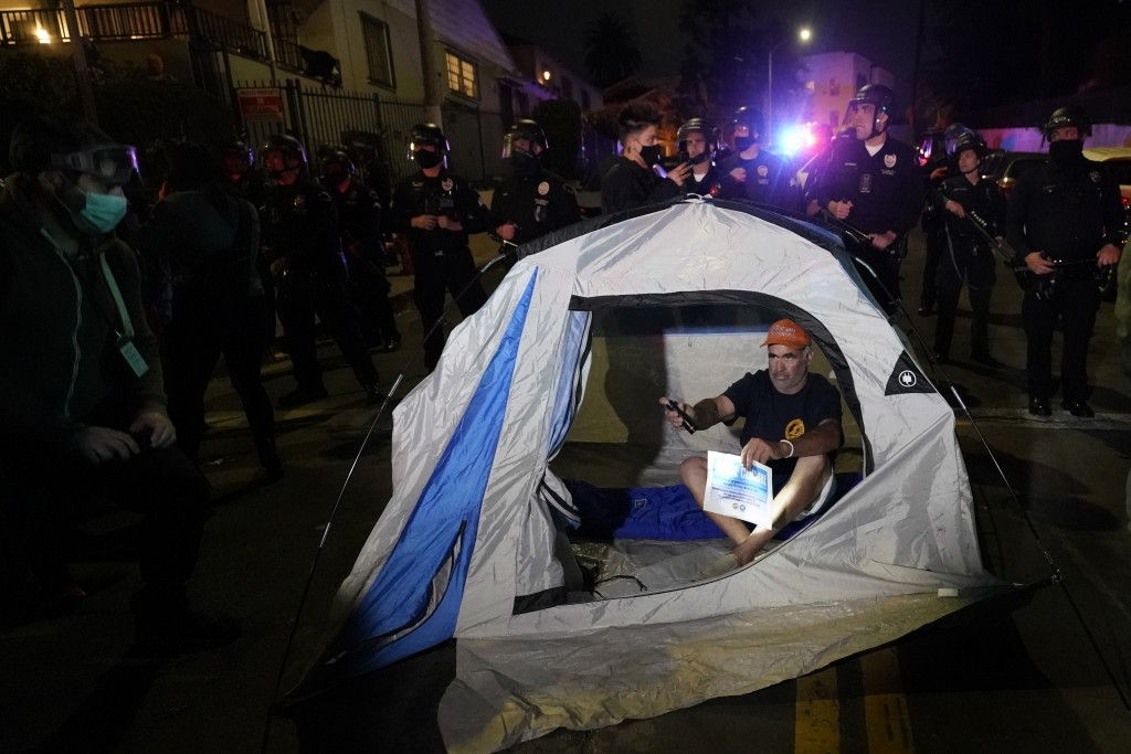 A demonstrator sets up a tent in front of police in the Echo Park section of Los Angeles Thursday, March 25, 2021. Demonstrators gathered Wednesday ni...