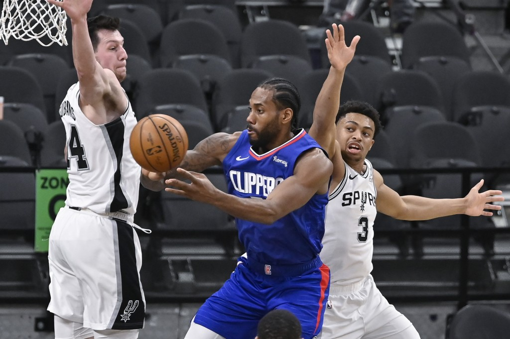 Los Angeles Clippers' Kawhi Leonard, center, passes the ball as he is defended by San Antonio Spurs' Drew Eubanks, left, and Keldon Johnson during the...
