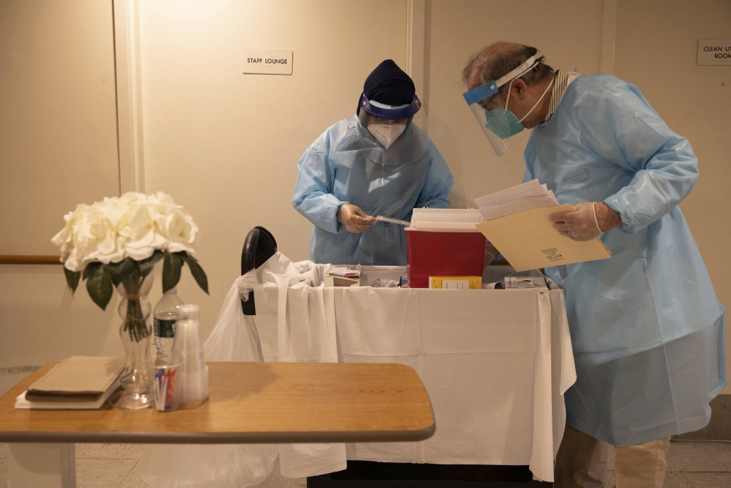 FILE - In this Jan. 15, 2021, file photo, CVS Pharmacists prepare the COVID-19 vaccine for the nursing home residents at Harlem Center for Nursing and...