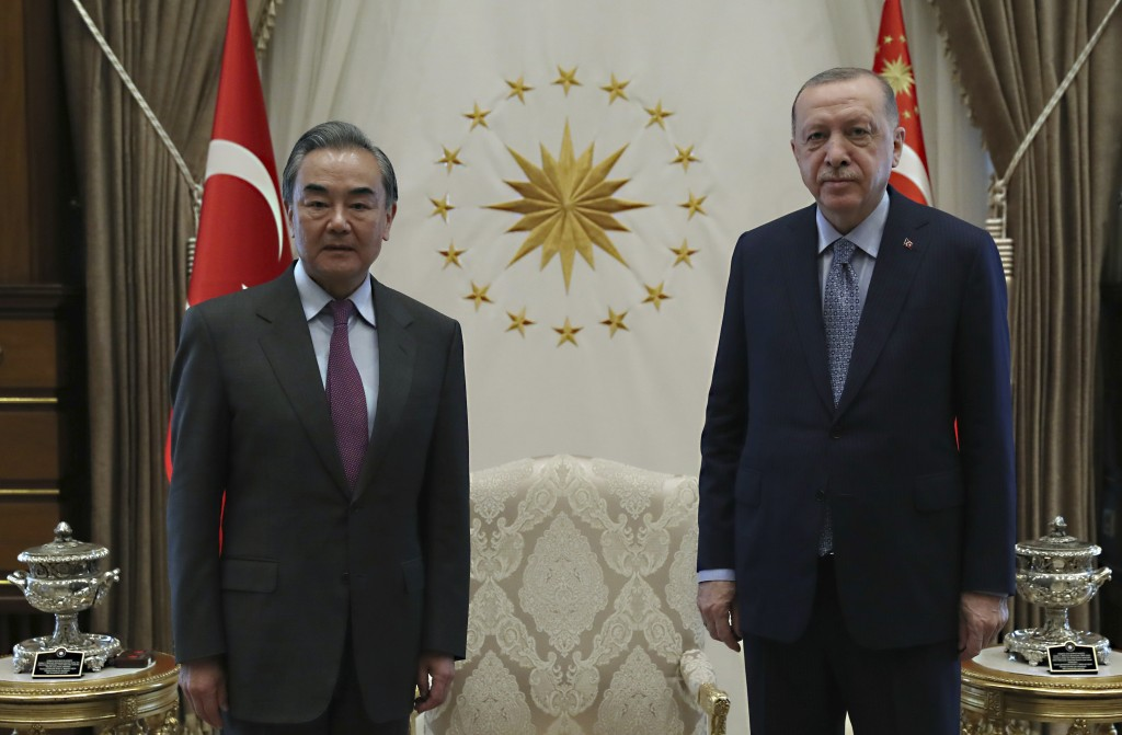 Turkey's President Recep Tayyip Erdogan, right, and Chinese Foreign Minister Wang Yi pose for photos before a meeting, in Ankara, Turkey, Thursday, Ma...
