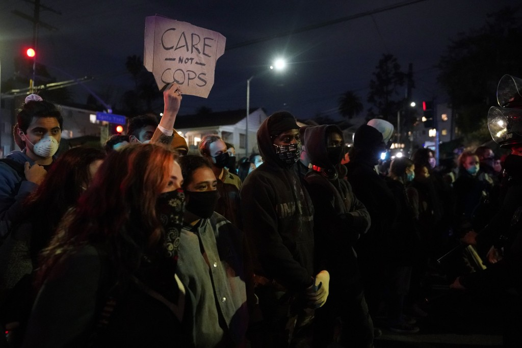 Demonstrators huddle in front of police in the Echo Park section of Los Angeles Thursday, March 25, 2021. Demonstrators gathered Wednesday night to pr...