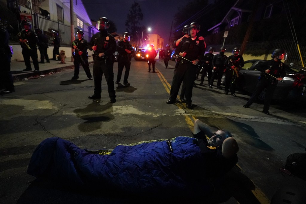 A demonstrator sets up a sleeping bag in front of police in the Echo Park section of Los Angeles Thursday, March 25, 2021. Demonstrators gathered Wedn...