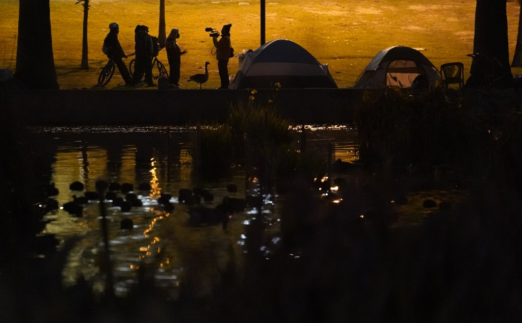 Members of the media interview demonstrators outside their tents in the Echo Park Lake homeless encampment in Los Angeles late Wednesday, March 24, 20...