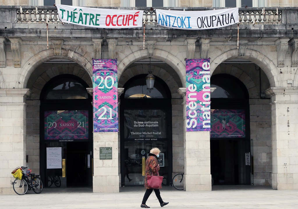 A woman walks past a theater with signs showing it occupied by culture workers, actors students and theater employees in Bayonne, southwestern France,...