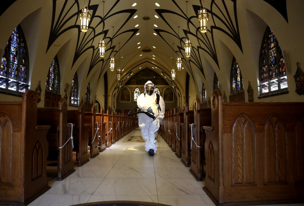 Disinfectant is sprayed on the pews between services at Our Lady of Sorrows in the Queens borough of New York on Sunday, March 21, 2021. The Roman Cat...