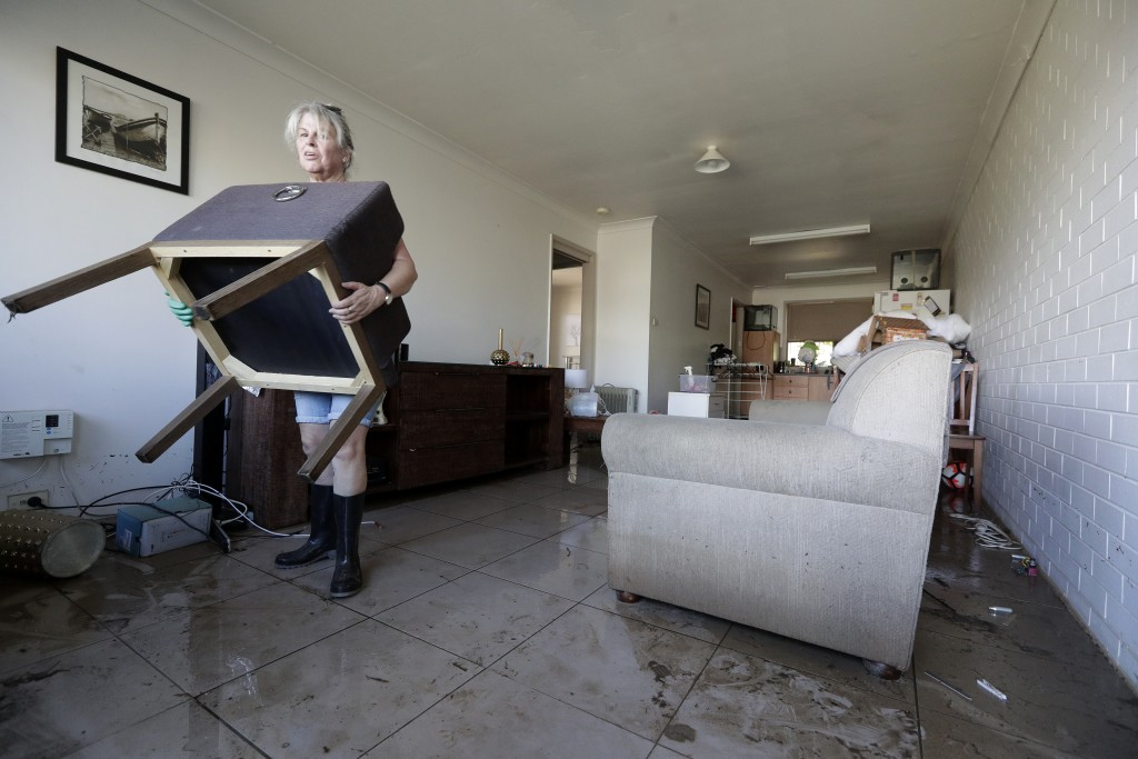 FILE - In this March 25, 2021, file photo, Dale Ward carries water-logged belongings out of her daughter's home after it was flooded in Windsor, north...