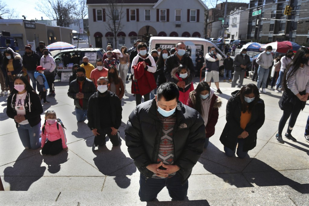Parishioners kneel during a Mass relayed via loudspeaker outside Our Lady of Sorrows in the Queens borough of New York on Sunday, March 21, 2021. The ...