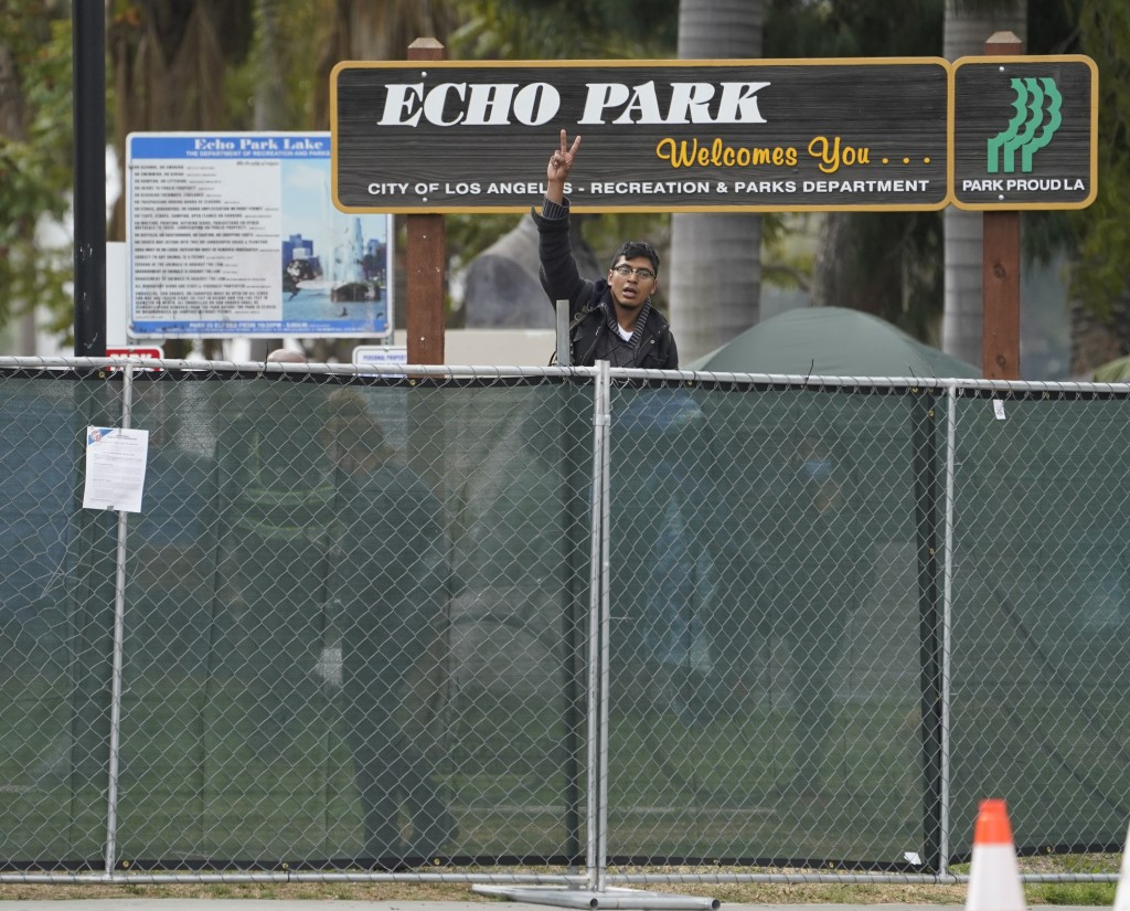 A homeless activist makes a peace sign gesture over a fence, as Los Angeles City sanitation workers move inside the closed perimeter of Echo Park Lake...