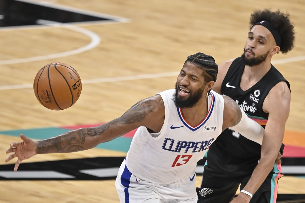 Los Angeles Clippers' Paul George (13) loses the ball as he is fouled by San Antonio Spurs' Derrick White during the second half of an NBA basketball ...