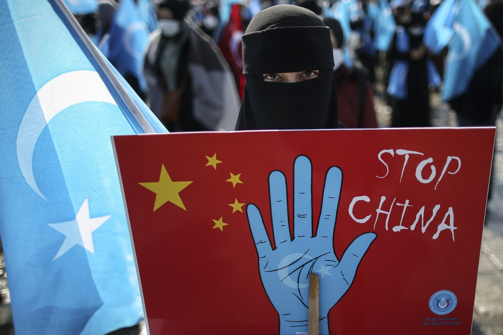A protester from the Uyghur community living in Turkey holds up an anti-China placard during a protest against the visit of China's Foreign Minister W...