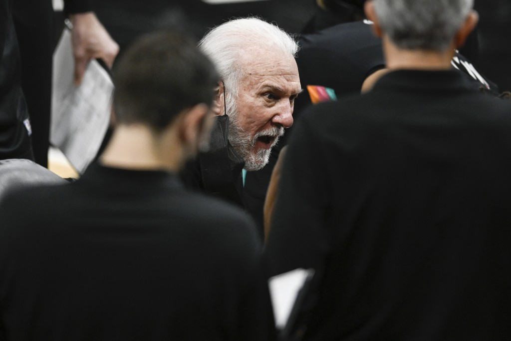 San Antonio Spurs head coach Gregg Popovich, center, talks to his players during a timeout in the first half of an NBA basketball game against the Los...