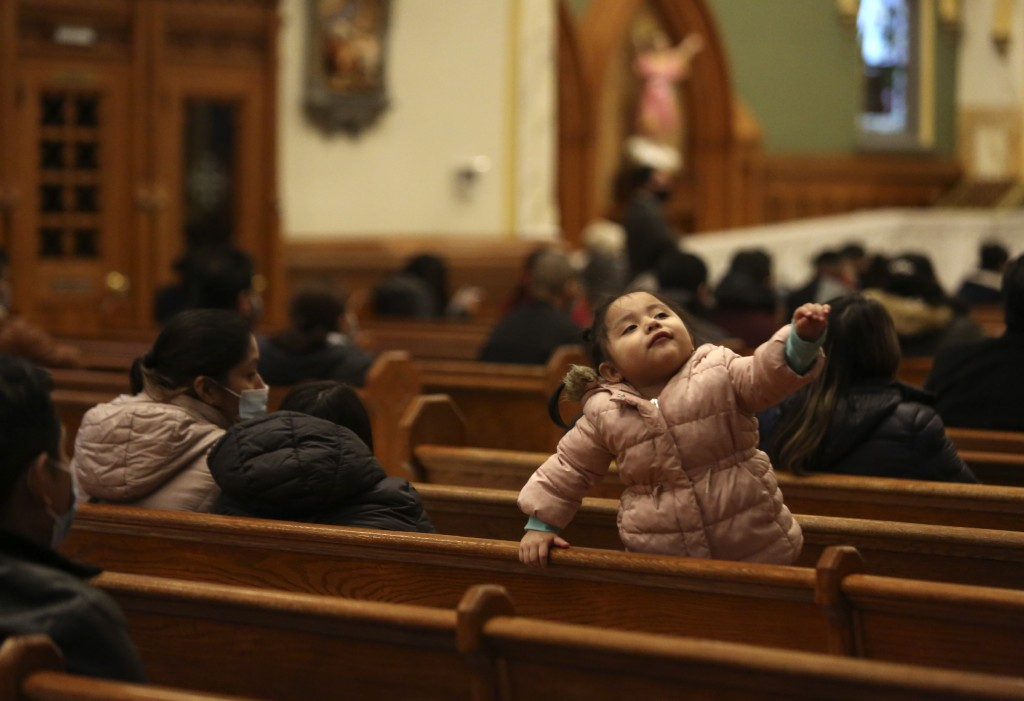 A child stands on a pew during Mass at Our Lady of Sorrows in the Queens borough of New York on Sunday, March 7, 2021. The Roman Catholic church reope...