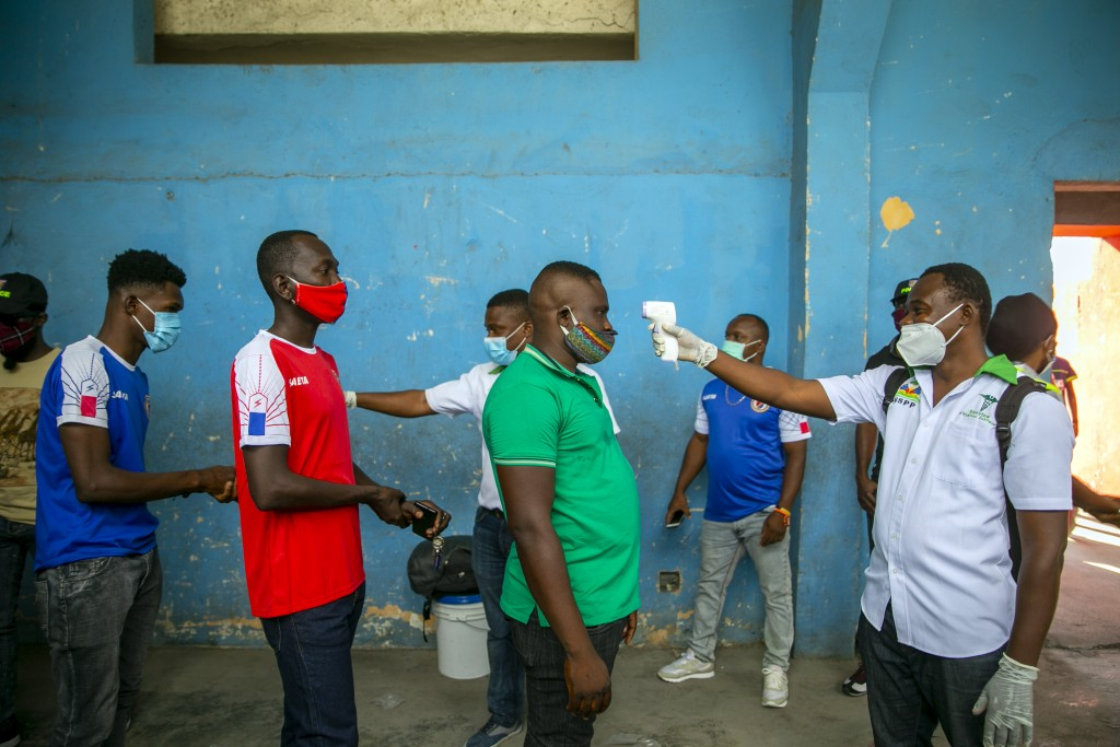 Health ministry workers check the temperature of mask-wearing fans as a precaution against the spread of the new coronavirus, before entering the stad...