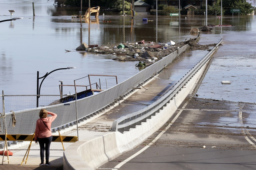 FILE - In this March 25, 2021, file photo, a woman looks at debris caught on a submerged bridge in Windsor, northwest of Sydney, Australia. Over recen...