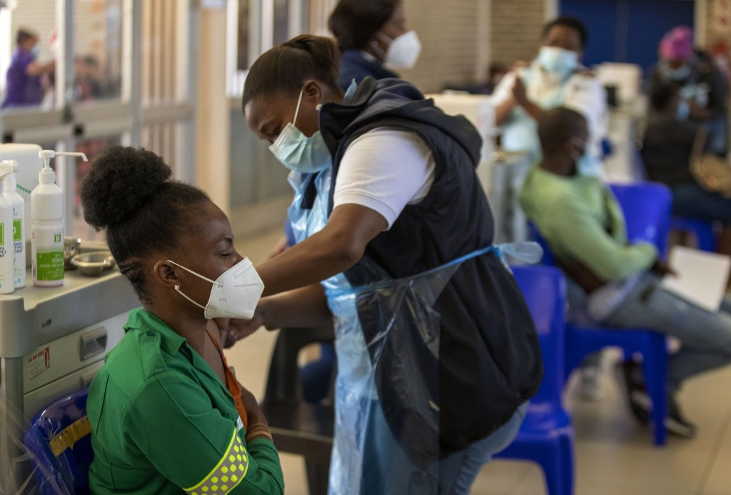 Khensani Chauke, a professional paramedic, receives a dose of Johnson & Johnson COVID-19 vaccine from a health staff member during a vaccination day f...