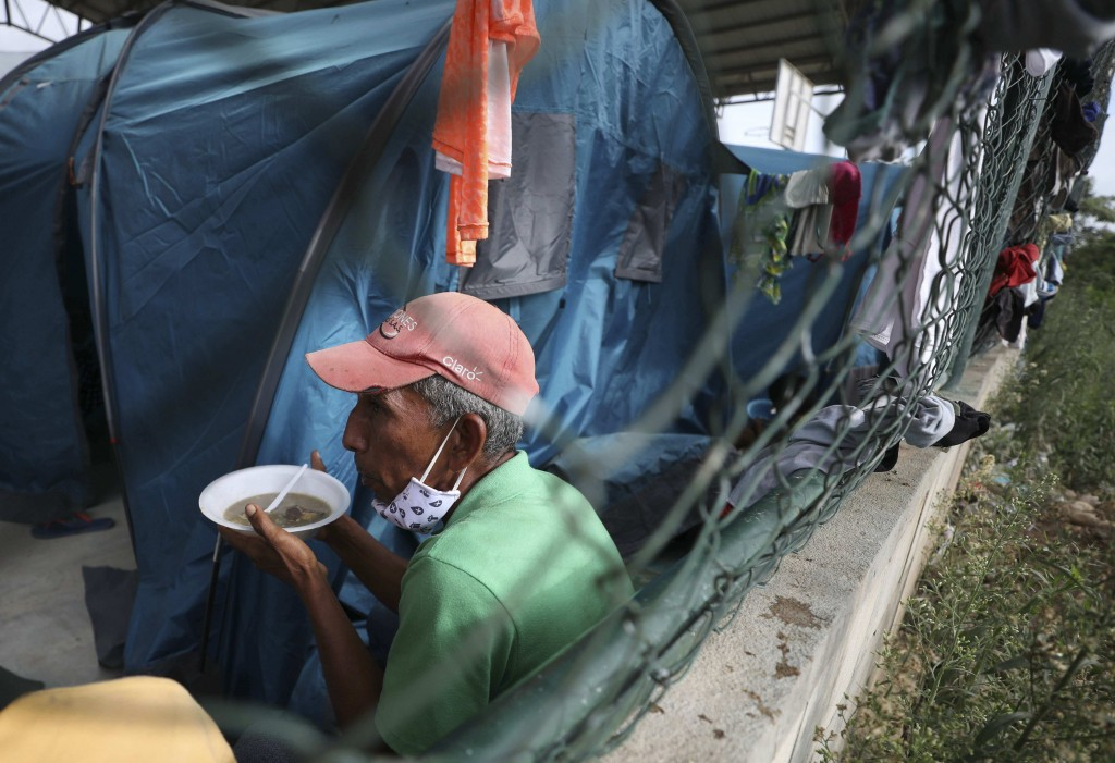 A Venezuelan sheltering at a community center gets a meal in Arauquita, Colombia, Thursday, March 25, 2021, on the border with Venezuela. Thousands of...