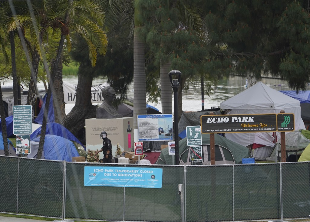 A Los Angeles Police officer walks under the Cuban national hero statue of Jose Marti, surrounded by homeless tents, inside Echo Park Lake's closed pe...