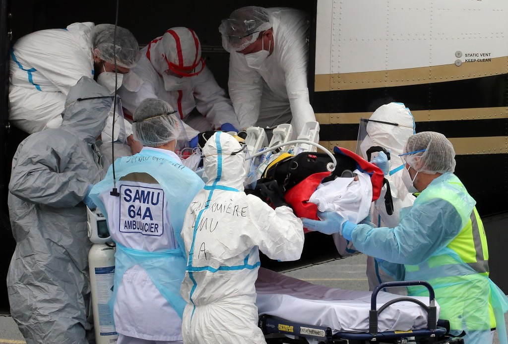 FILE- In this March 19, 2021, file photo, a patient from the Paris region and affected by the COVID-19 virus is taken out a plane at the Biarritz's ai...