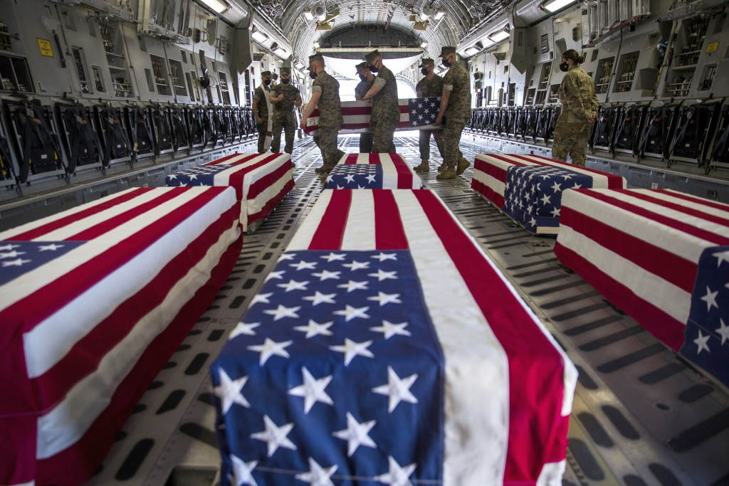 FILE - In this Aug. 12, 2020, file photo, provided by the U.S. Marine Corps, U.S. Marines and sailors carry a casket inside a U.S. Air Force C-17 Glob...