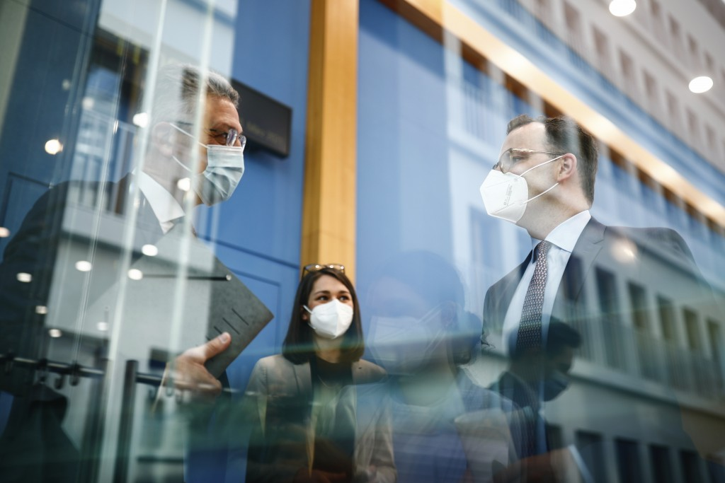 Germany's Health Minister Jens Spahn, right, talks to Lothar Wieler, the head of Germany's Robert Koch Institute (RKI) for disease control after a  ne...