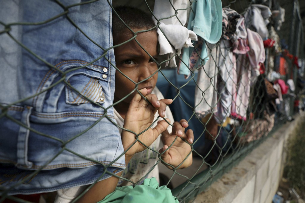 A child looks through a fence of a shelter at a community center in Arauquita, Colombia, Thursday, March 25, 2021, on the border with Venezuela. Thous...