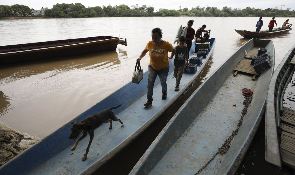 Venezuelans carry their belongings after using a boat to cross the Arauca River, the natural border between Venezuela and Colombia, as they arrive to ...