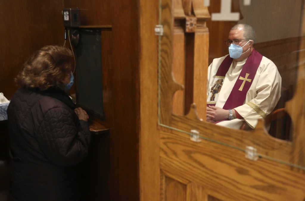 The Rev. Manuel Rodriguez listens to a parishioner's confession at Our Lady of Sorrows in the Queens borough of New York on Saturday, March 20, 2021. ...