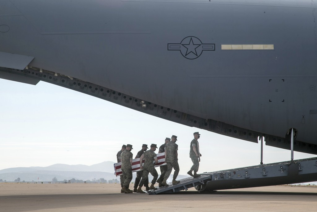 FILE - In this Aug. 12, 2020, file photo, provided by the U.S. Marine Corps, U.S. Marines and sailors carry a casket aboard a U.S. Air Force C-17 Glob...