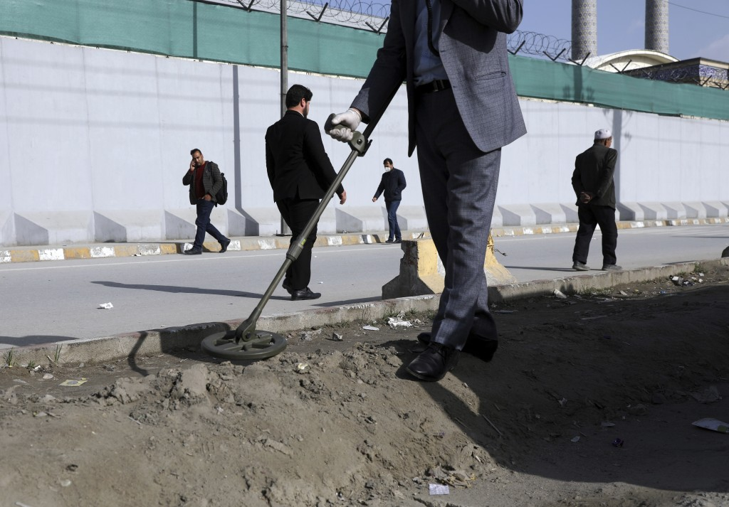 An Afghan security official looks for mines or improvised explosive device with metal detector on a roadside during a trip organized by the police for...
