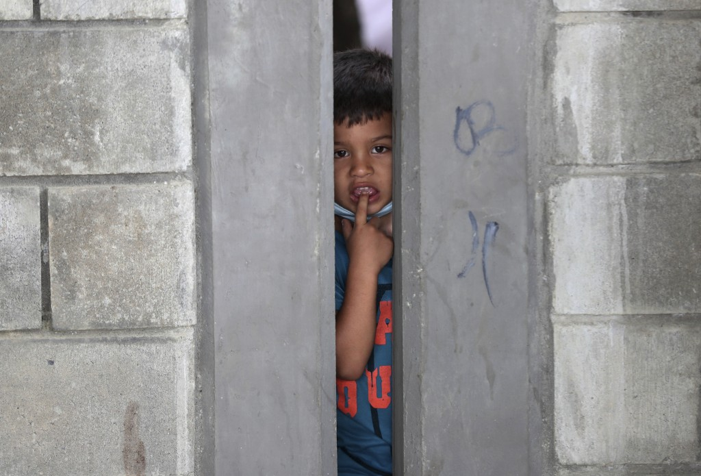 A boy peers from a migrant shelter in Arauquita, Colombia, Thursday, March 25, 2021, on the border with Venezuela. Thousands of Venezuelans are seekin...