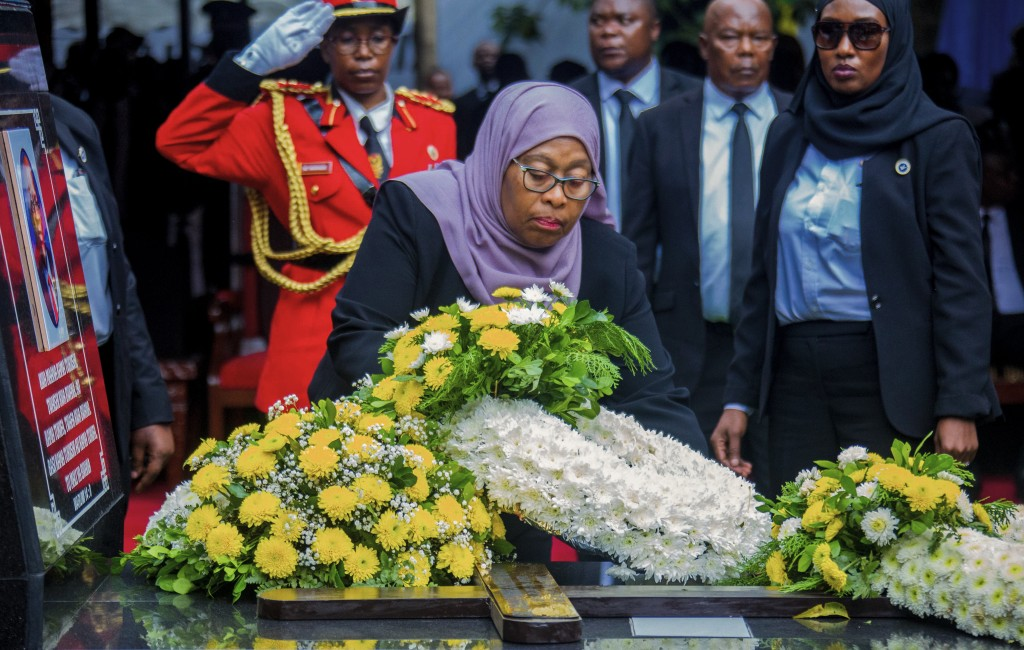President Samia Suluhu Hassan places flowers on the grave of former President John Magufuli in his home town of Chato, Tanzania Friday, March 26, 2021...